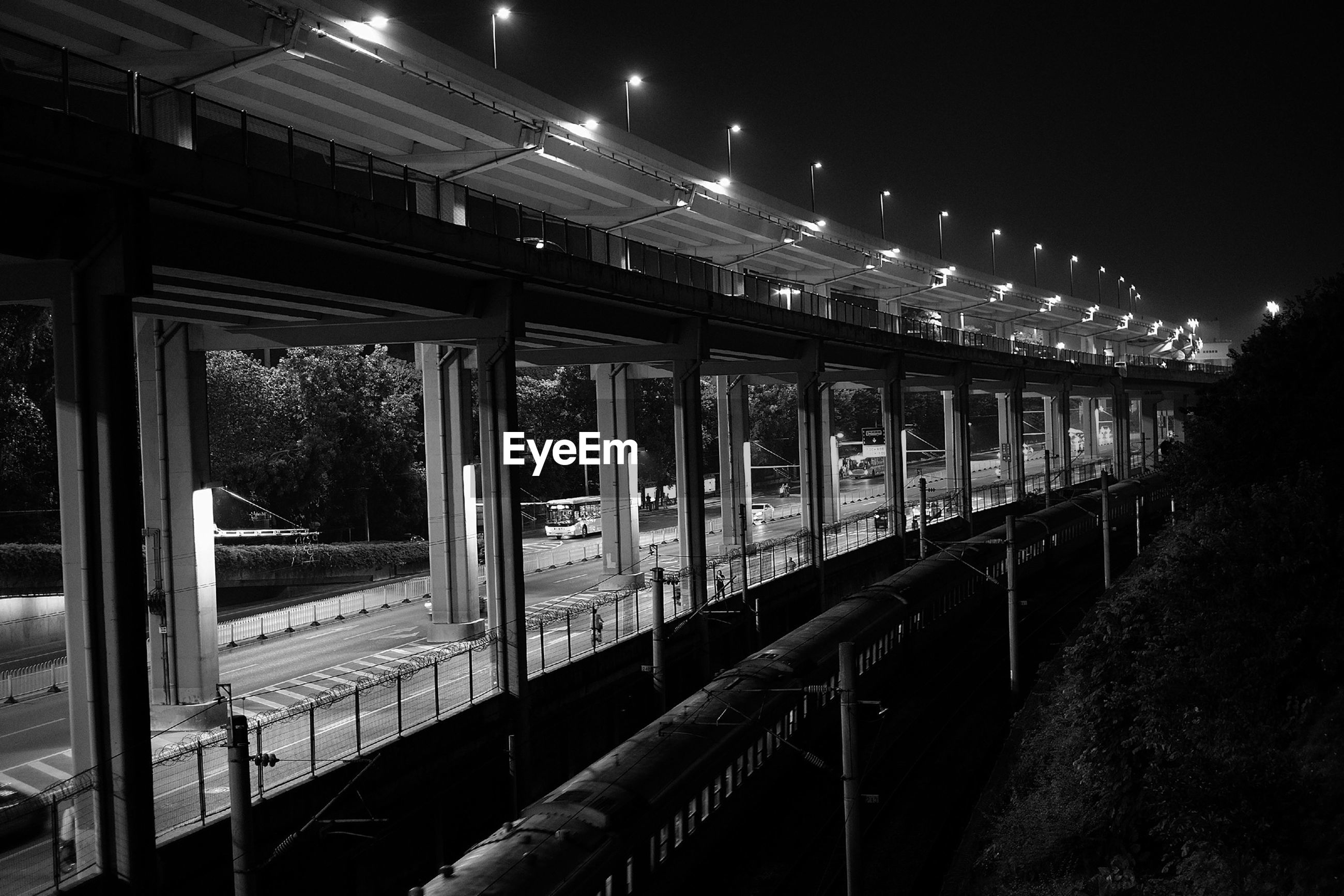 Train moving by bridge during night