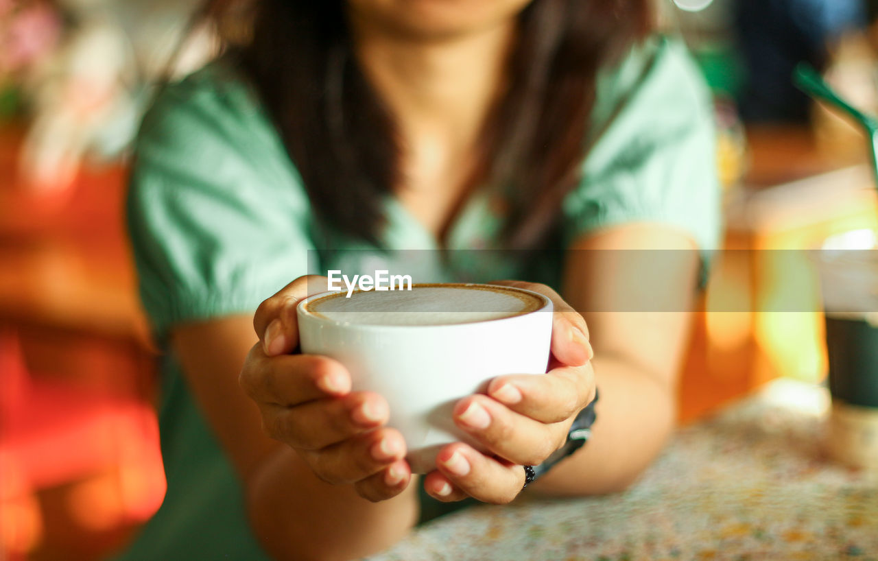 CLOSE-UP OF WOMAN DRINKING COFFEE CUP