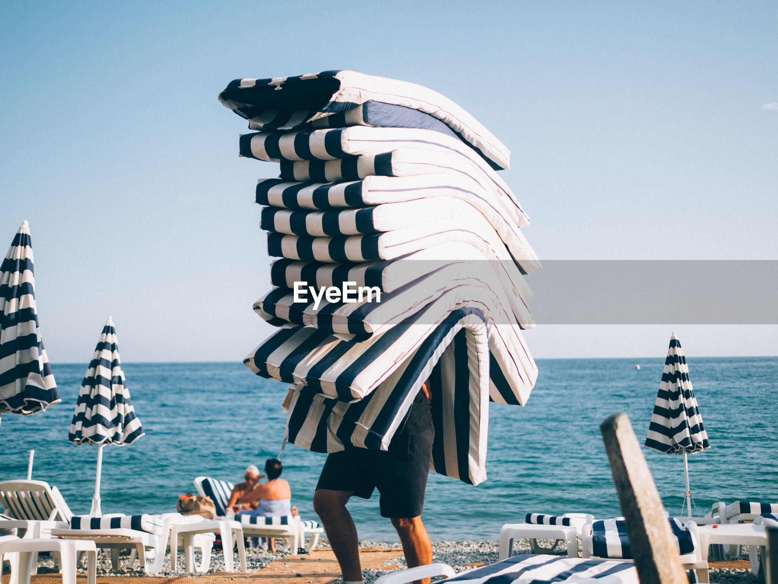 Person carrying cushions on beach