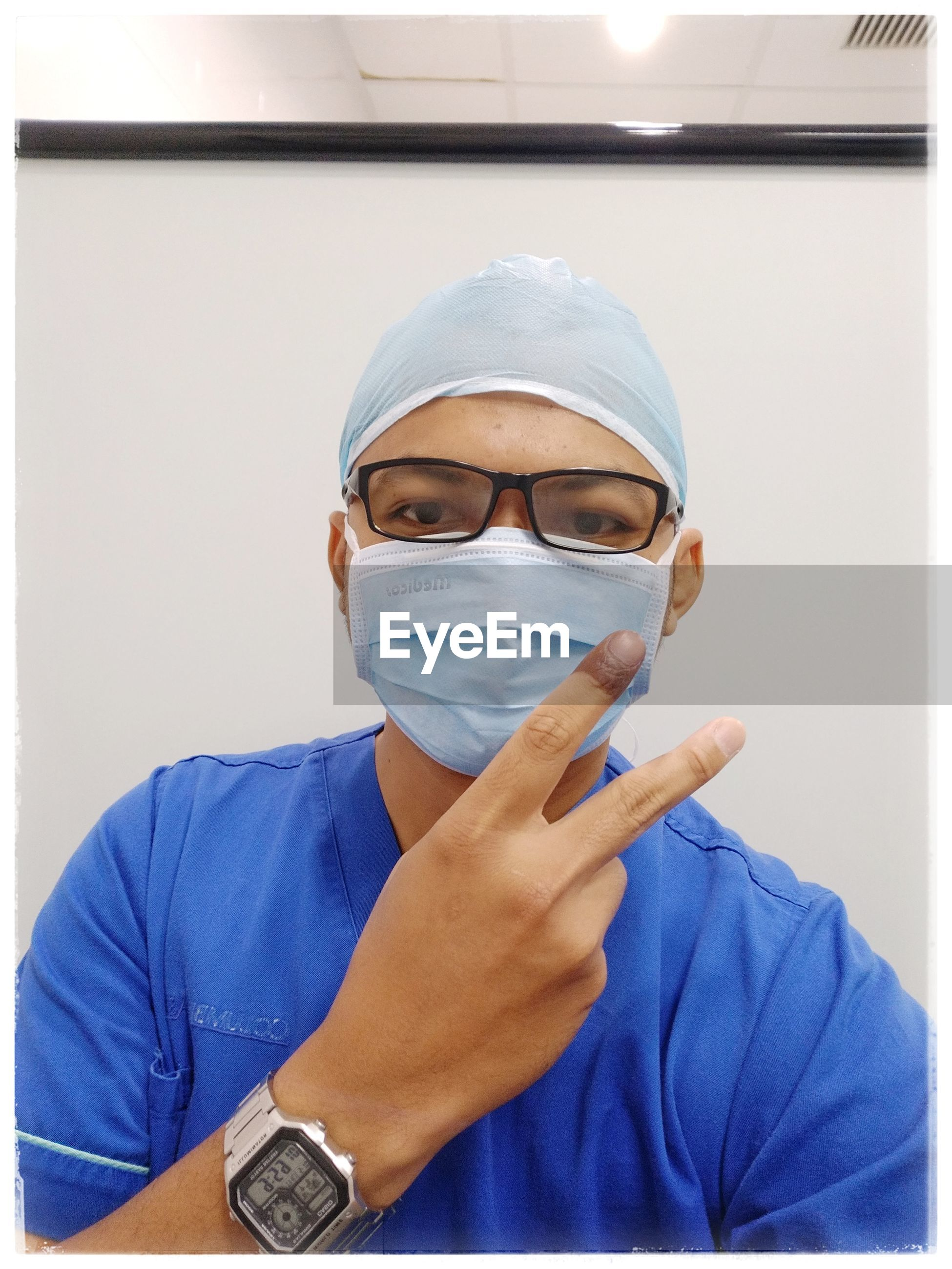 Portrait of doctor wearing mask while gesturing at hospital