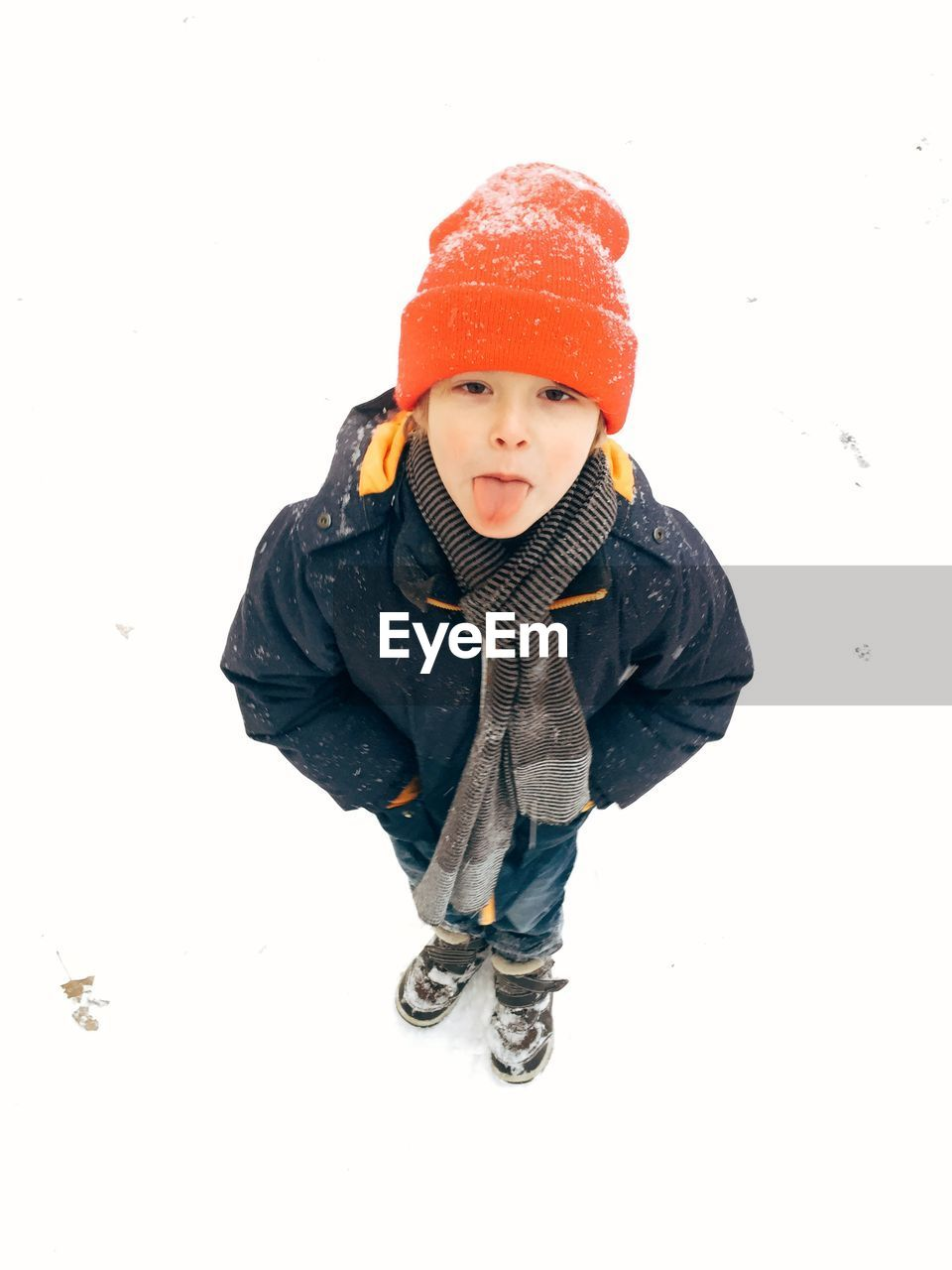 High angle portrait of boy sticking out tongue while standing on snow covered field