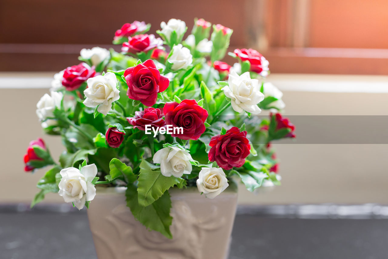 flower, flowering plant, rose, rose - flower, plant, flower arrangement, beauty in nature, fragility, red, vulnerability, freshness, bouquet, flower head, nature, indoors, table, focus on foreground, petal, close-up, vase, no people, bunch of flowers