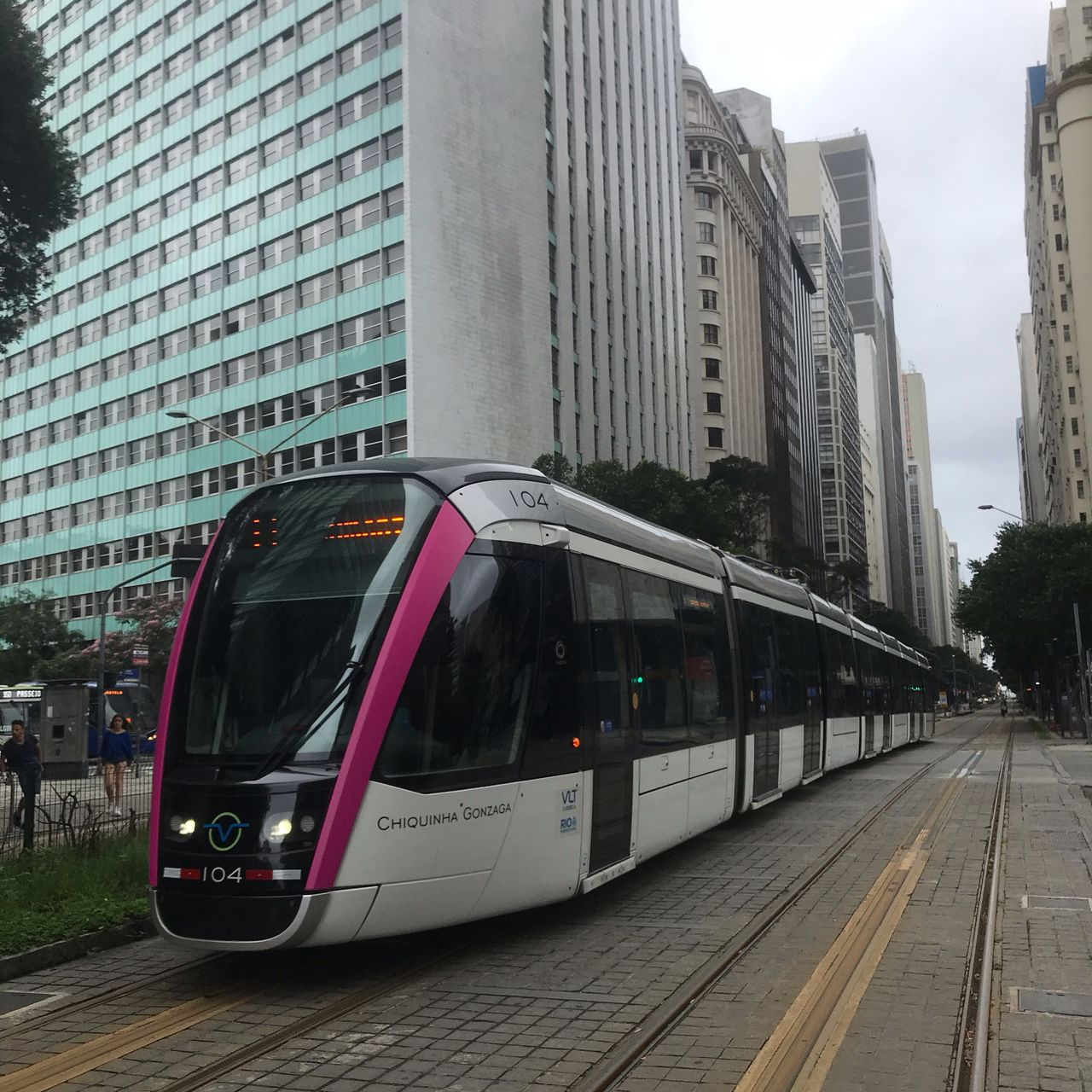 architecture, transportation, public transportation, rail transportation, mode of transportation, built structure, building exterior, city, track, railroad track, train, building, train - vehicle, day, outdoors, travel, motion, no people, land vehicle, office building exterior, skyscraper, financial district