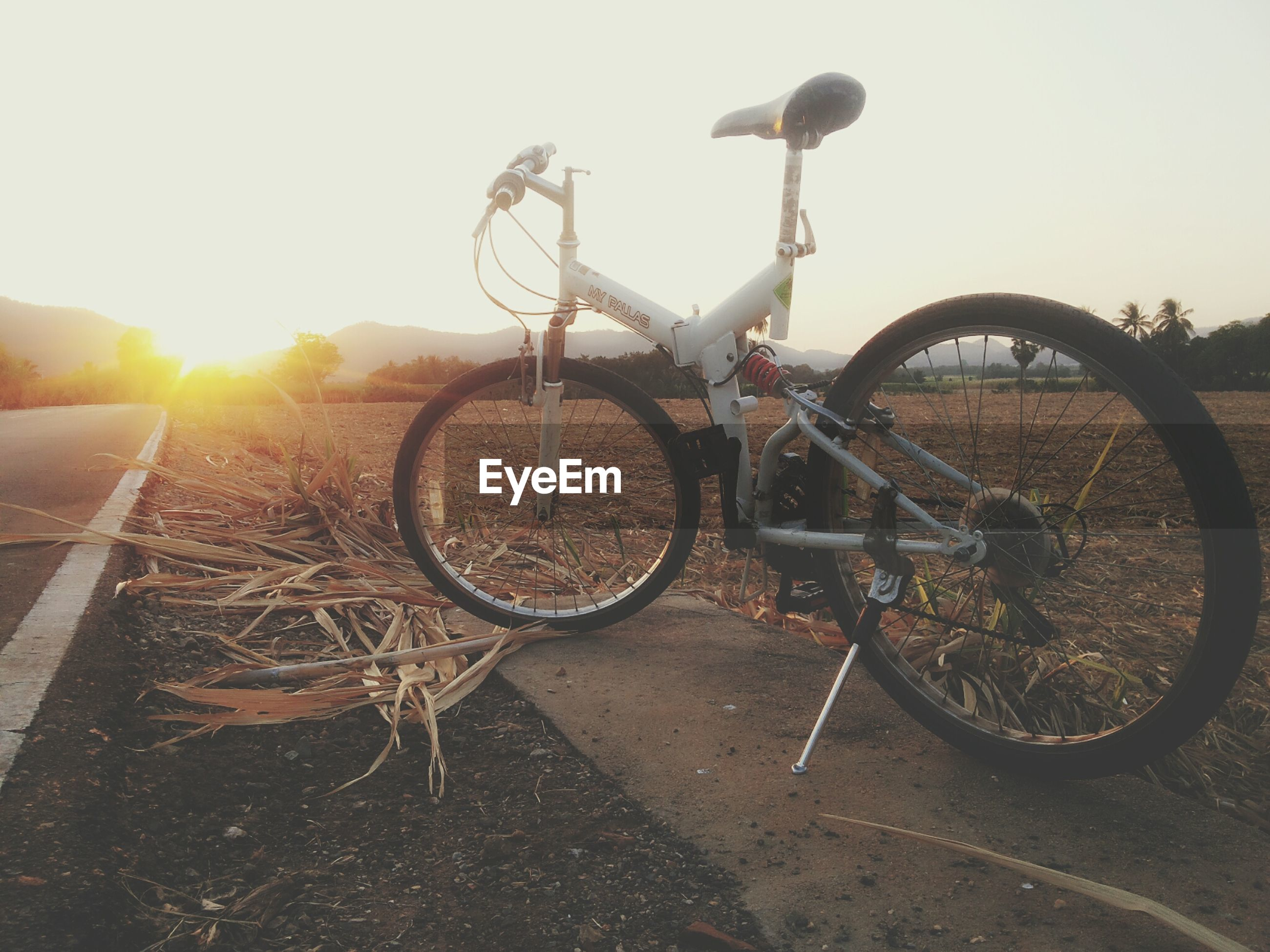 transportation, bicycle, land vehicle, mode of transport, stationary, parked, wheel, parking, field, sunlight, clear sky, sky, outdoors, rural scene, landscape, no people, plant, day, agriculture, sunset