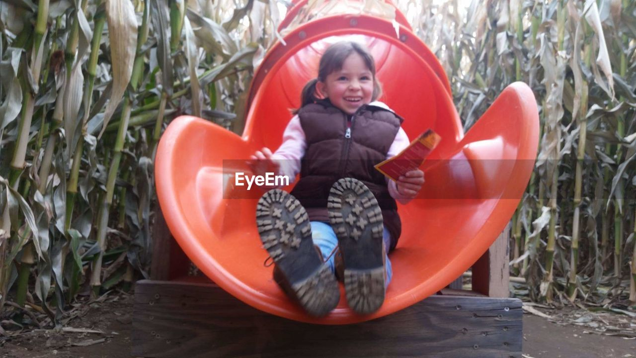 full length, child, one person, childhood, smiling, emotion, innocence, happiness, sitting, front view, plant, looking at camera, nature, day, clothing, leisure activity, real people, enjoyment, outdoors, warm clothing, rubber boot