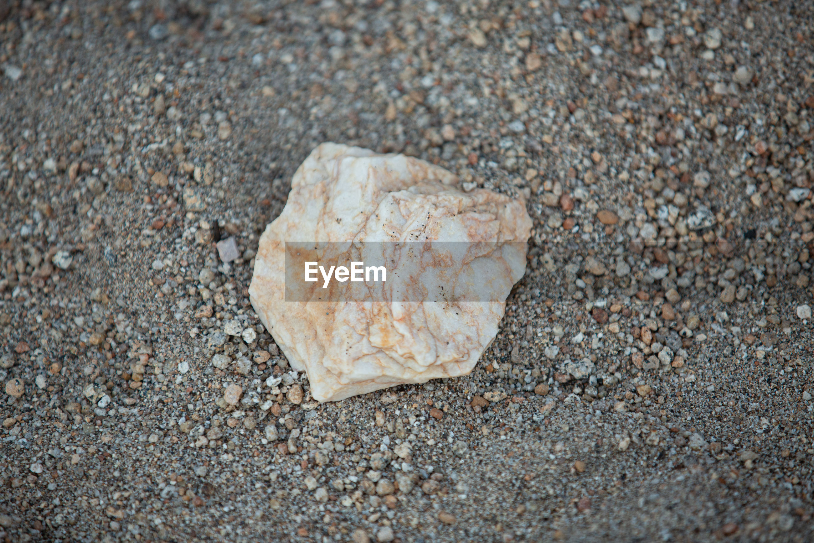 CLOSE-UP OF STONE ON SAND