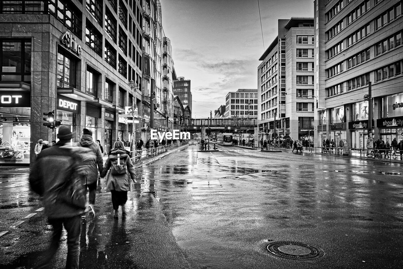 city, building exterior, architecture, street, built structure, wet, water, walking, real people, transportation, city life, building, rain, men, group of people, day, women, nature, city street, rainy season, outdoors