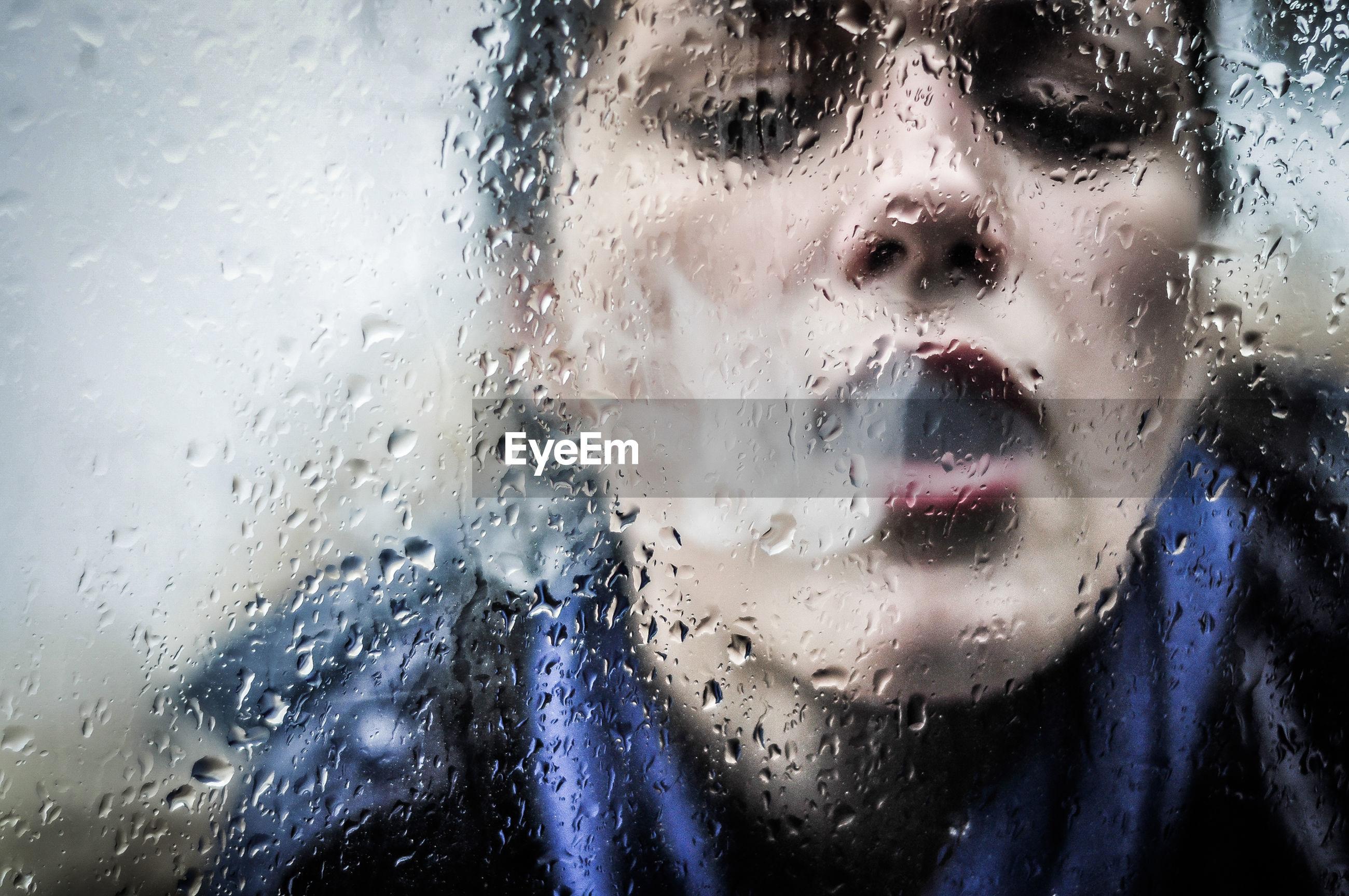 Close-up of woman emitting smoke on wet glass