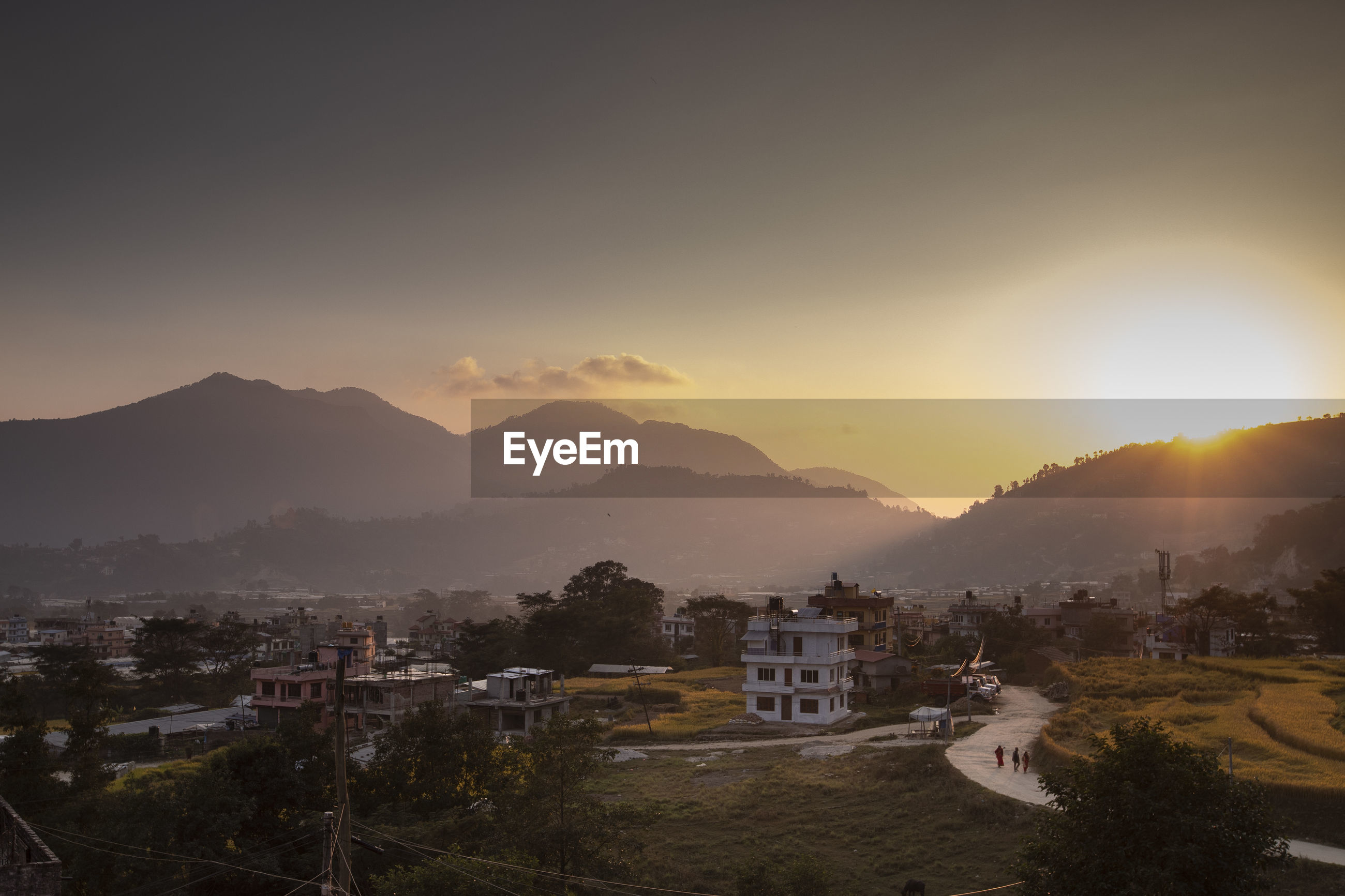 HIGH ANGLE VIEW OF TOWNSCAPE AND MOUNTAINS AGAINST SKY DURING SUNSET