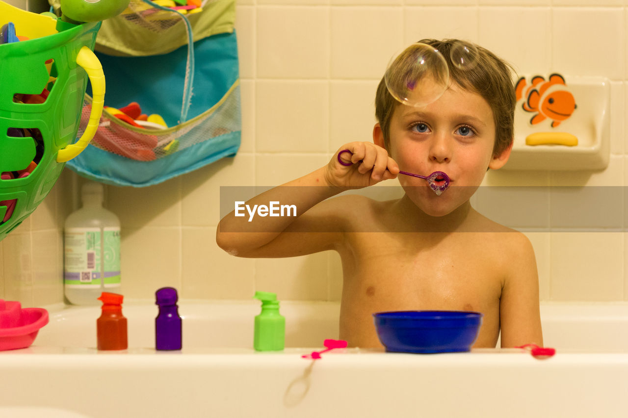 Portrait of shirtless boy blowing bubbles in bathroom