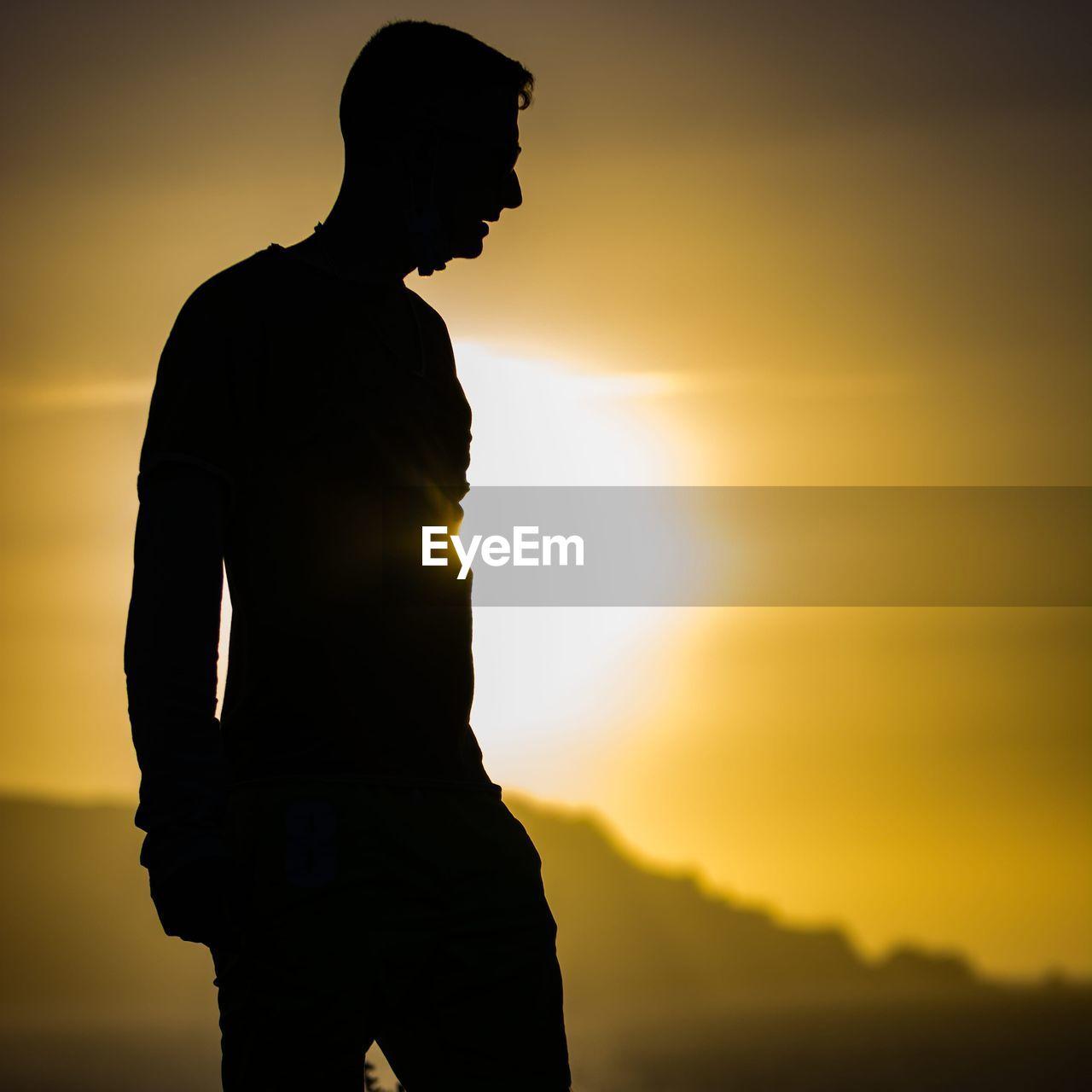 SILHOUETTE MAN STANDING AGAINST ORANGE SUNSET SKY