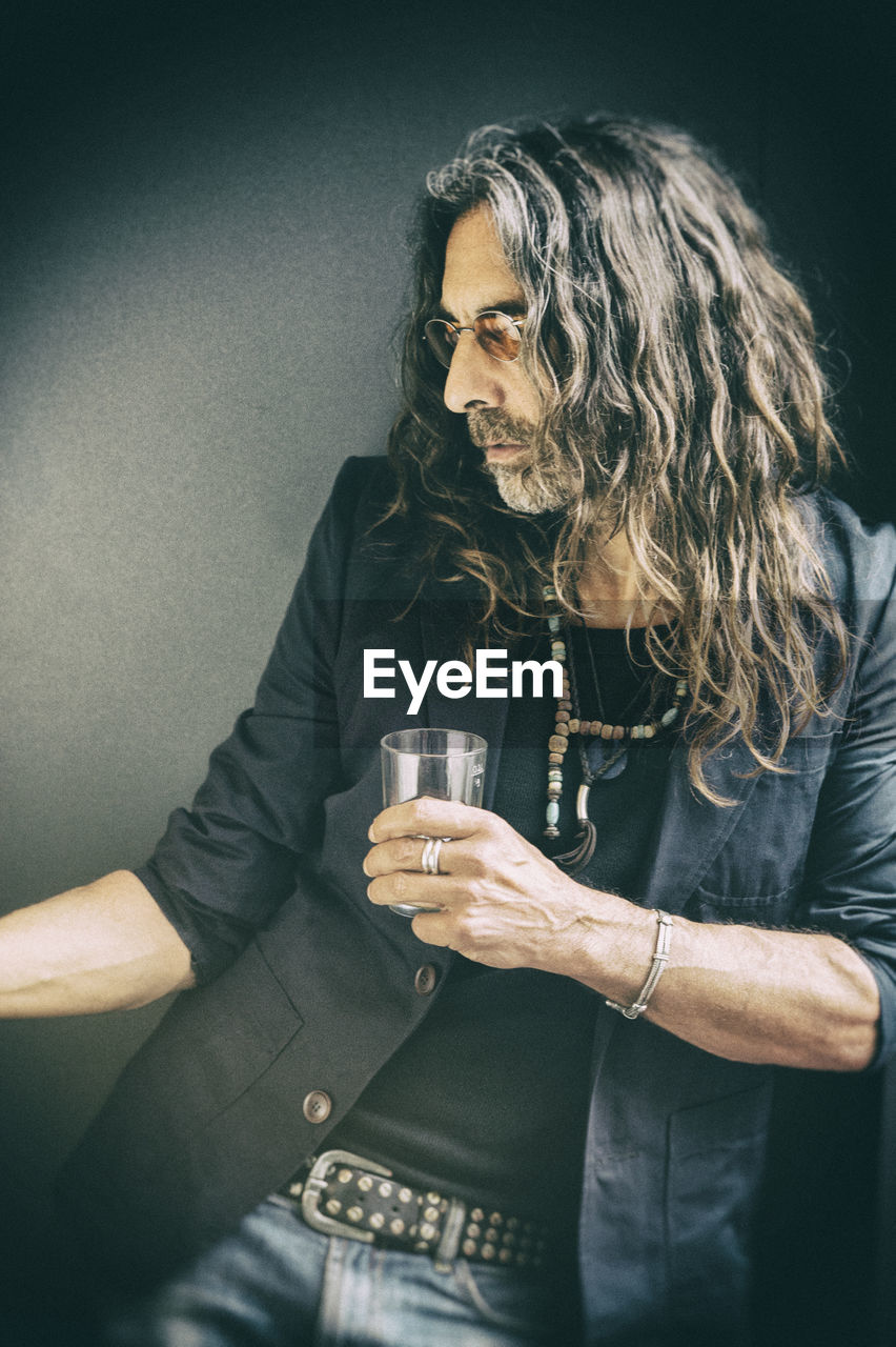 Man holding drinking glass on black background