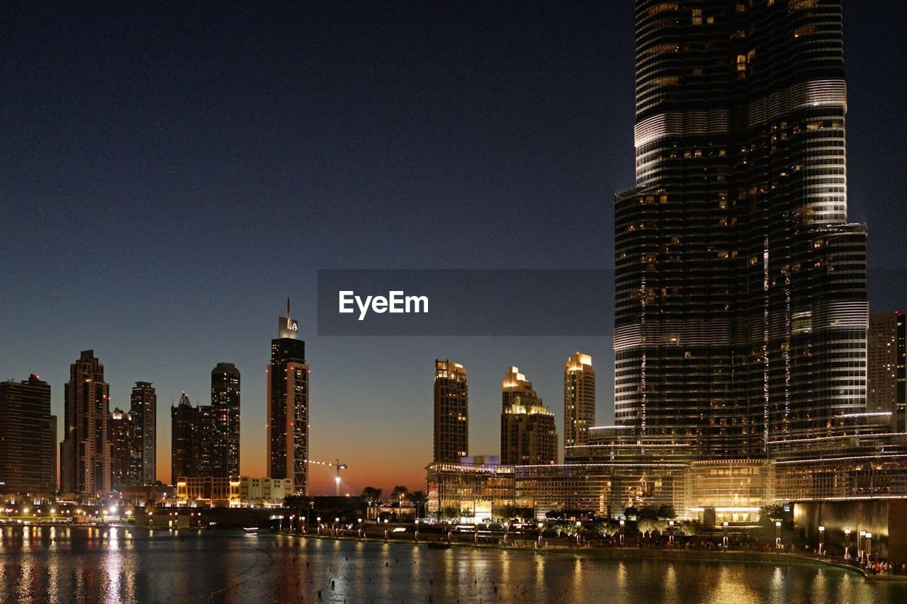 Illuminated Burj Khalifa And Skyscrapers By River At Night