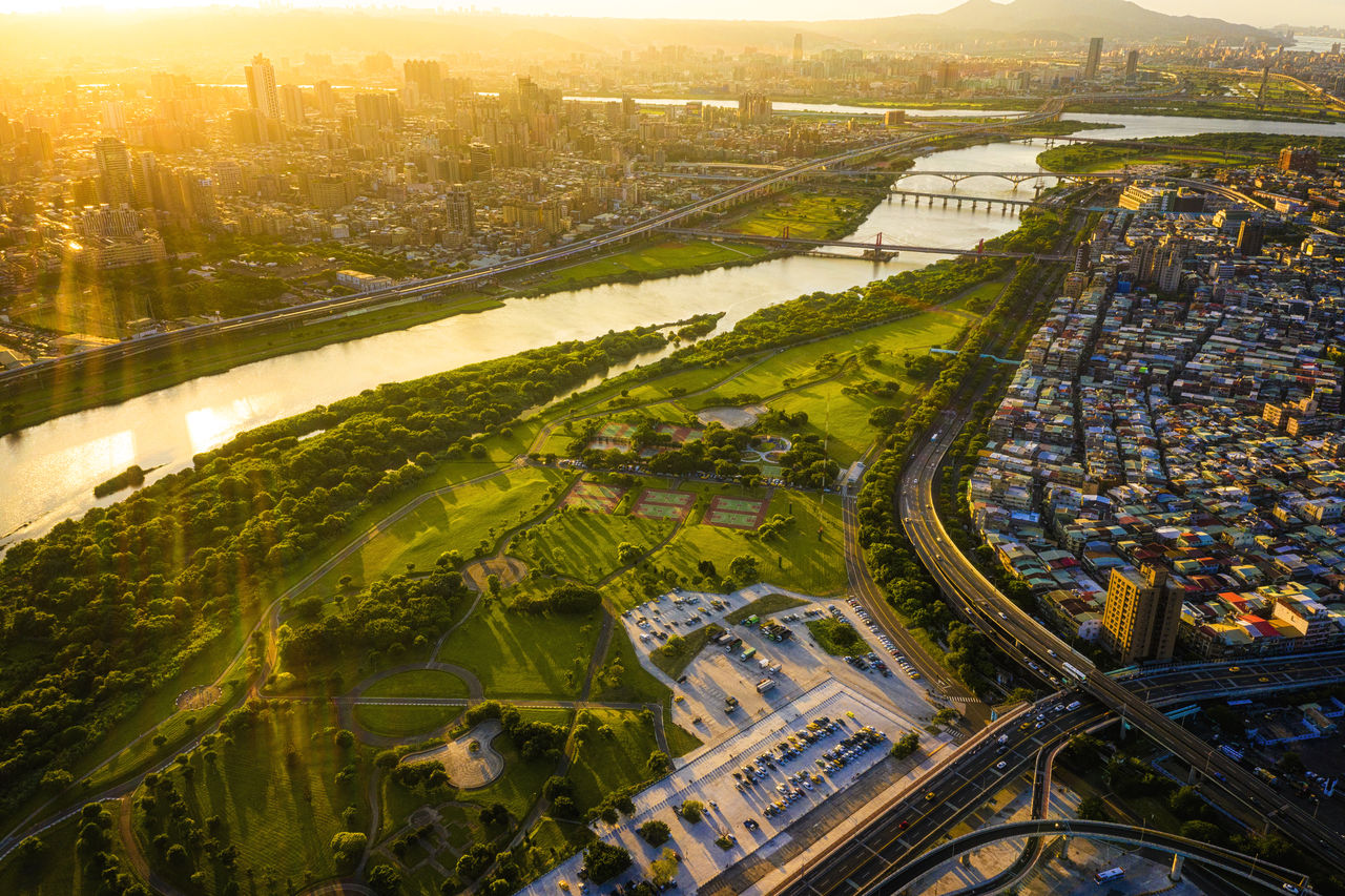 city, architecture, cityscape, building exterior, aerial view, built structure, high angle view, transportation, nature, road, residential district, sky, city life, highway, building, day, no people, outdoors, travel destinations, connection, bridge - man made structure, multiple lane highway, overpass, modern, skyscraper, office building exterior