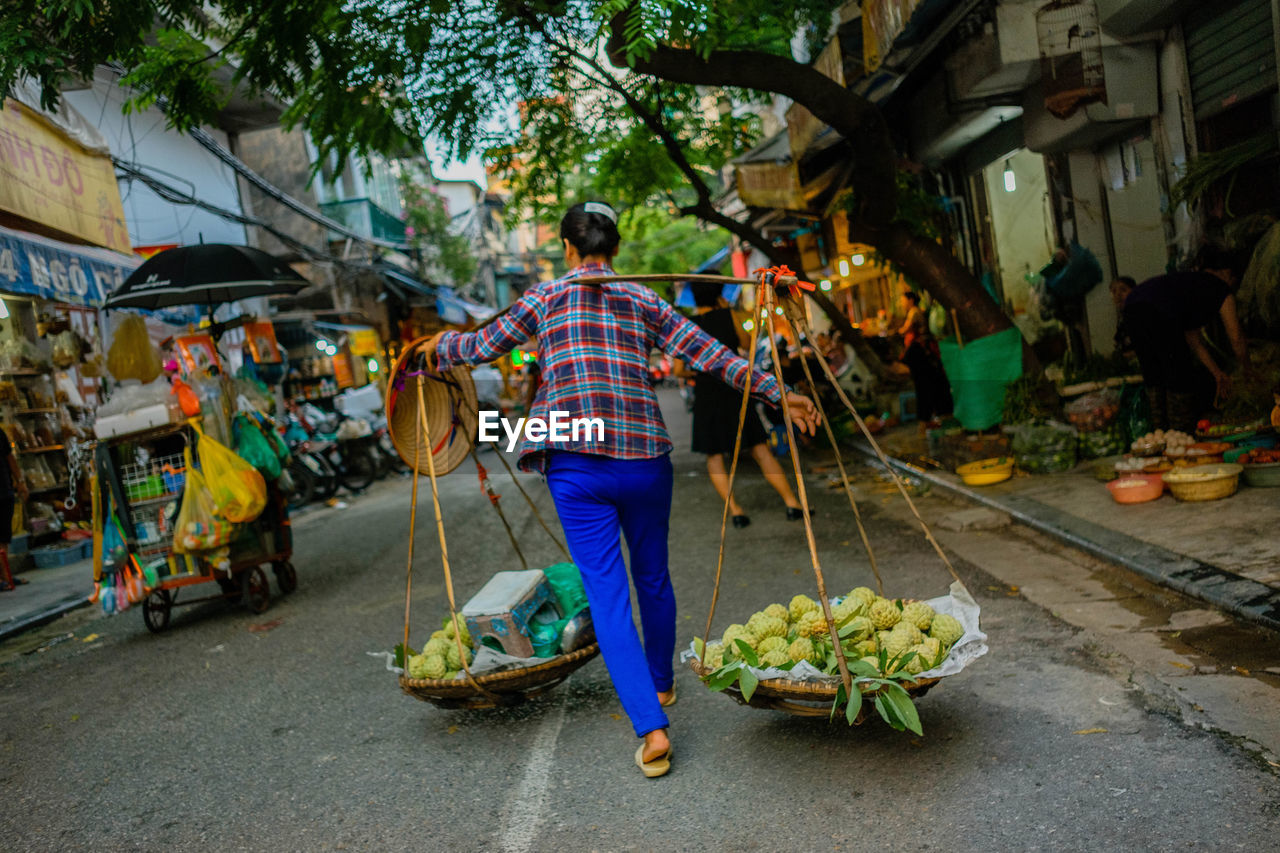 REAR VIEW OF MAN HOLDING FOOD IN MARKET STALL