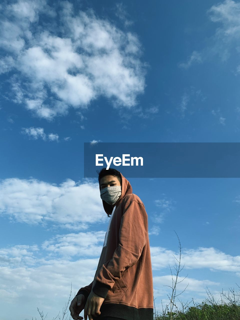 Low angle view of man wearing mask against sky
