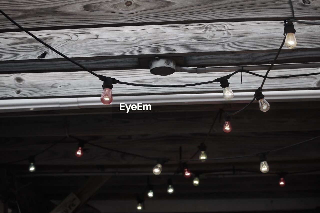 low angle view, ceiling, hanging, indoors, illuminated, lighting equipment, no people, architecture, built structure, electricity, day, light bulb, cable, rope, roof, decoration, wood - material