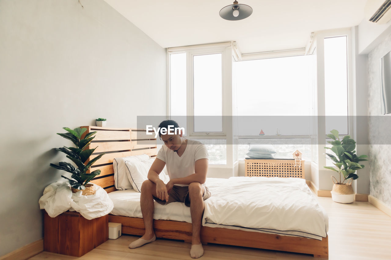Lonely and depressed man in his bedroom in the apartment.