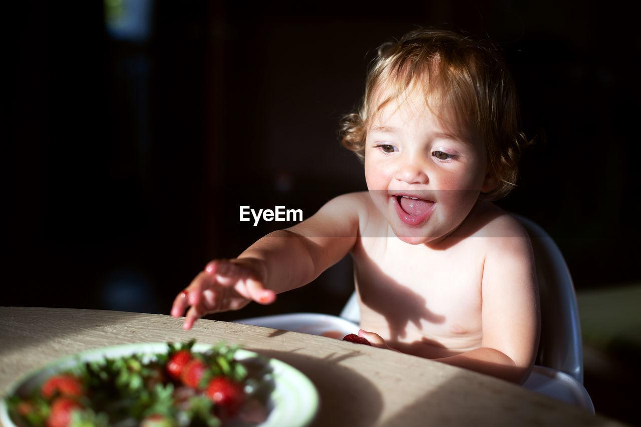 Cute baby girl reaching towards food in plate