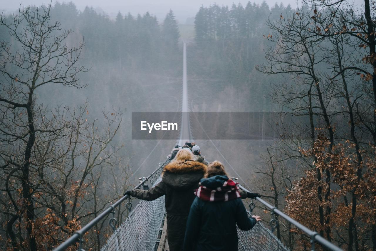 Rear View Of People Walking On Footbridge Amidst Trees During Foggy Weather