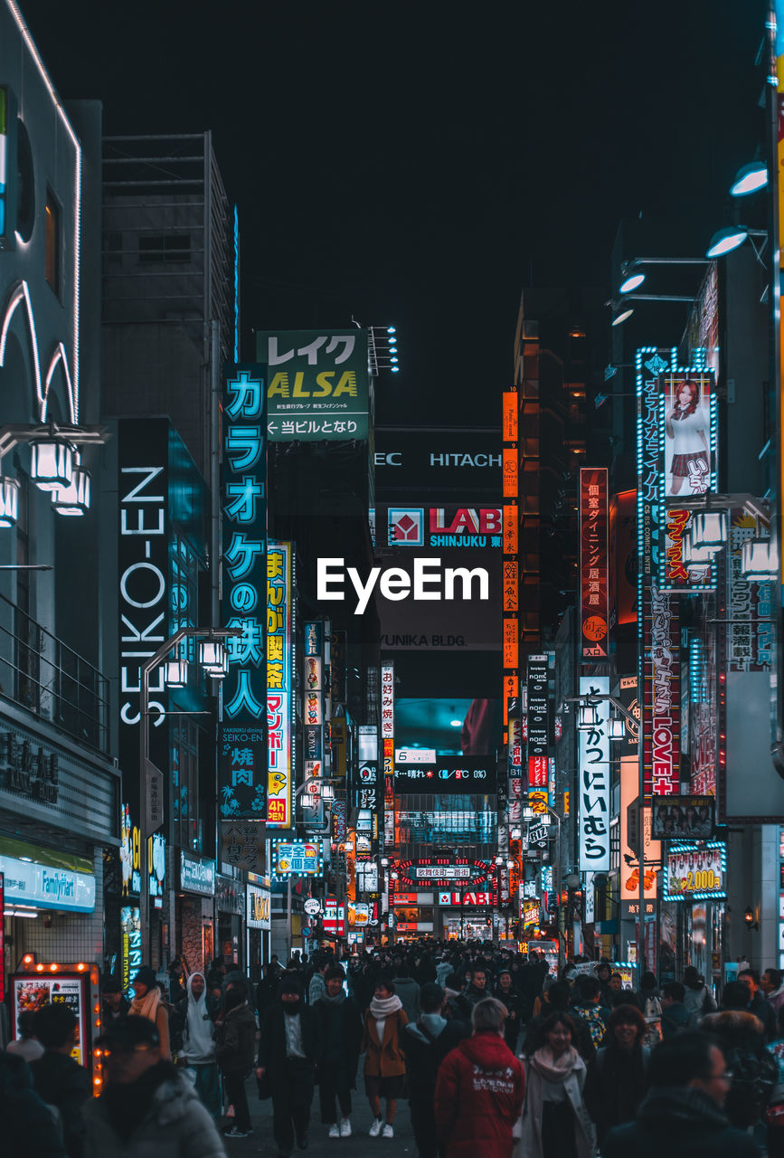 illuminated, night, city, crowd, building exterior, group of people, real people, large group of people, architecture, built structure, text, communication, city life, advertisement, street, commercial sign, script, lifestyles, non-western script, neon, outdoors, nightlife