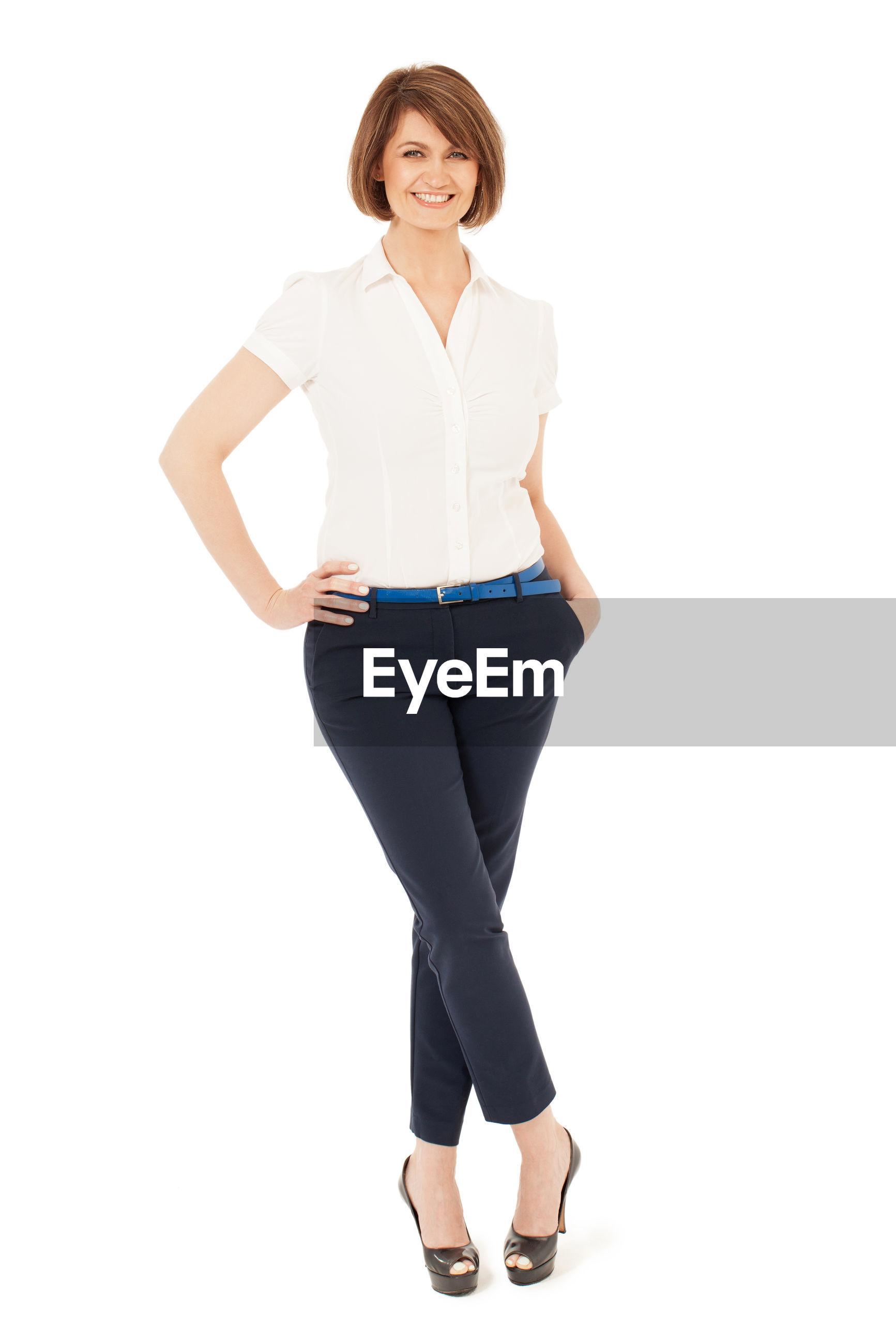 Full length portrait of confident businesswoman standing against white background