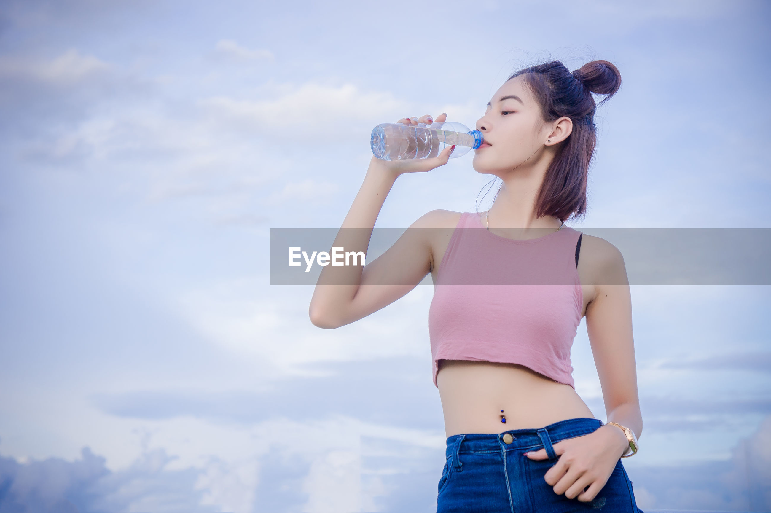 Young woman drinking water from bottle against sky