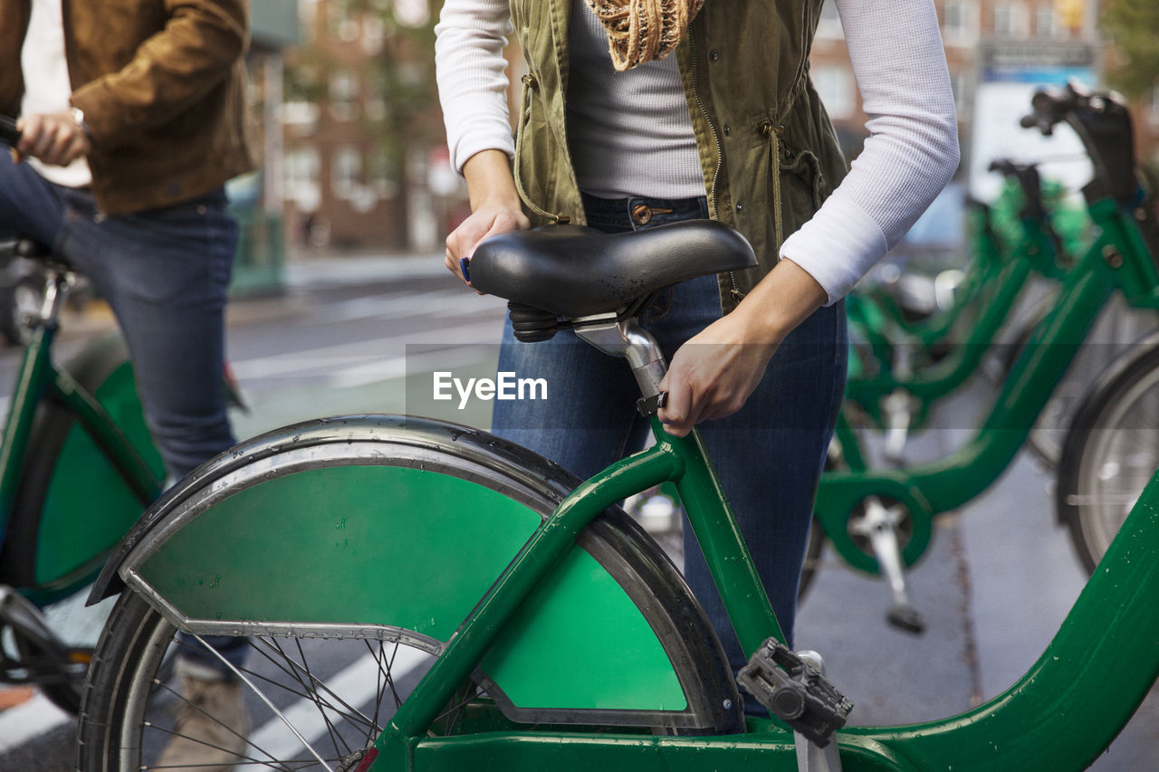 REAR VIEW OF WOMAN RIDING BICYCLE ON CITY