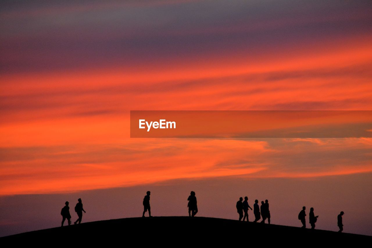 sunset, sky, group of people, silhouette, orange color, real people, lifestyles, men, scenics - nature, cloud - sky, medium group of people, beauty in nature, group, leisure activity, nature, people, land, walking, unrecognizable person, women, outdoors, horizon over water