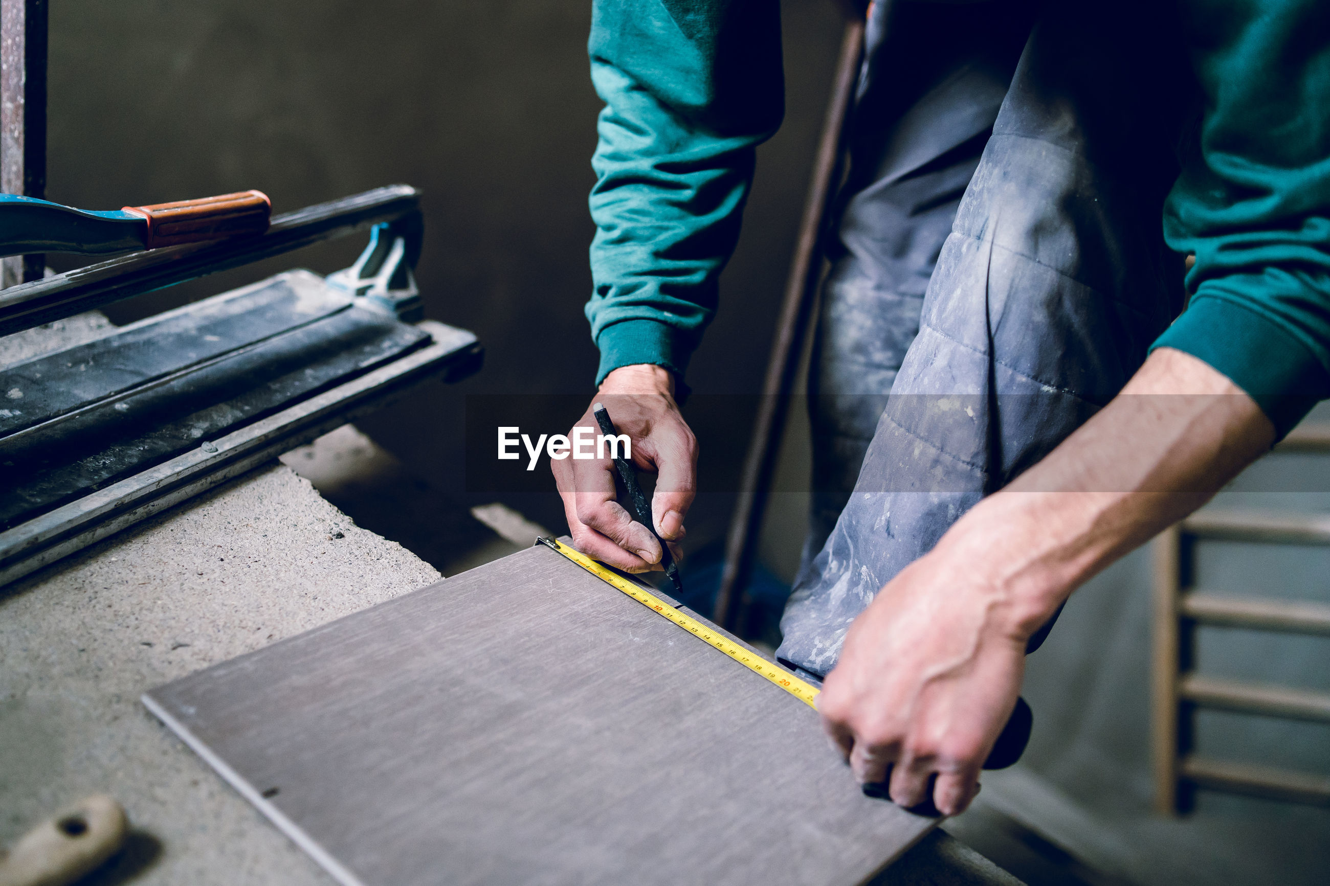 Cropped image of male worker measuring wood at table