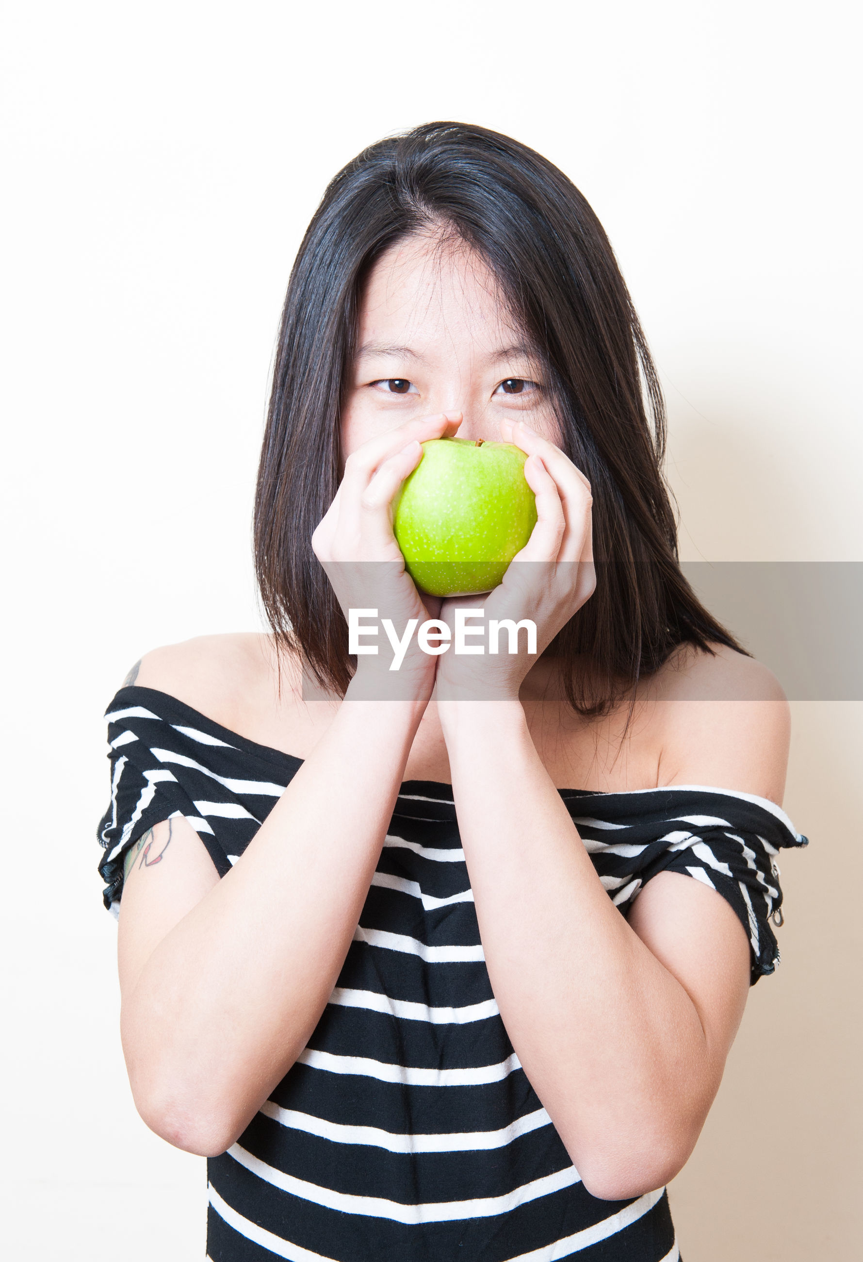 Portrait of woman holding fruit while standing against white background