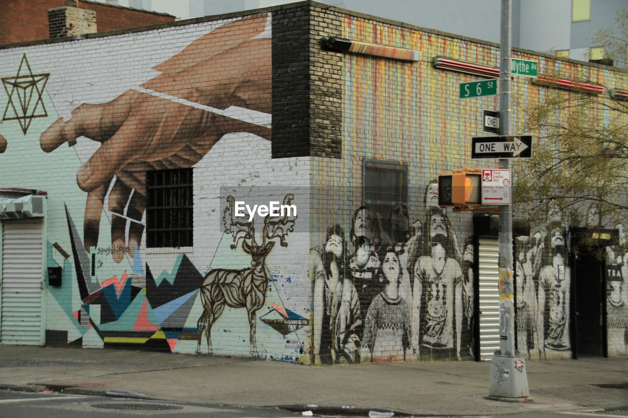 building exterior, architecture, built structure, building, city, graffiti, art and craft, no people, day, creativity, street, human representation, representation, window, outdoors, wall - building feature, nature, house, wall, multi colored, mural