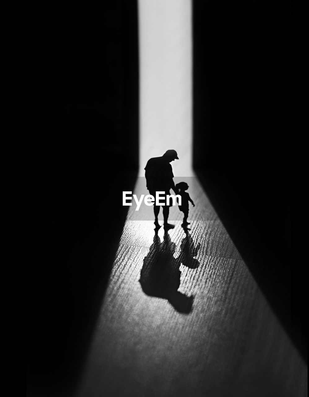 SILHOUETTE PEOPLE WITH TOY STANDING ON FLOOR IN DARK