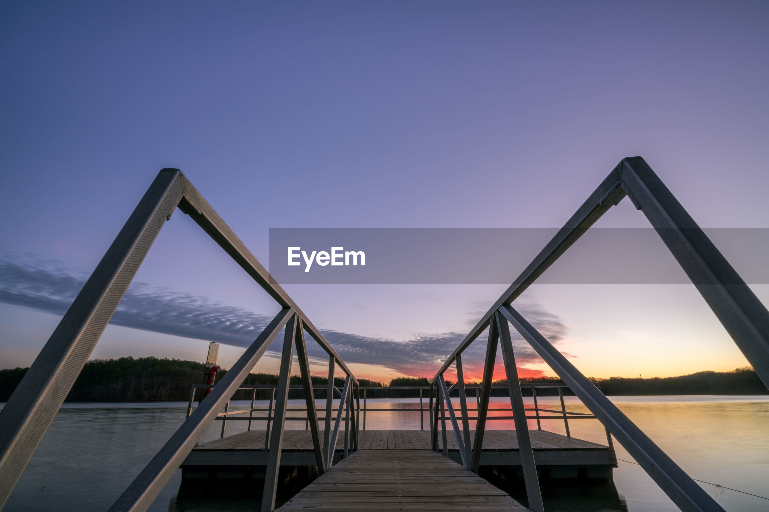 Pier over river against sky during sunset