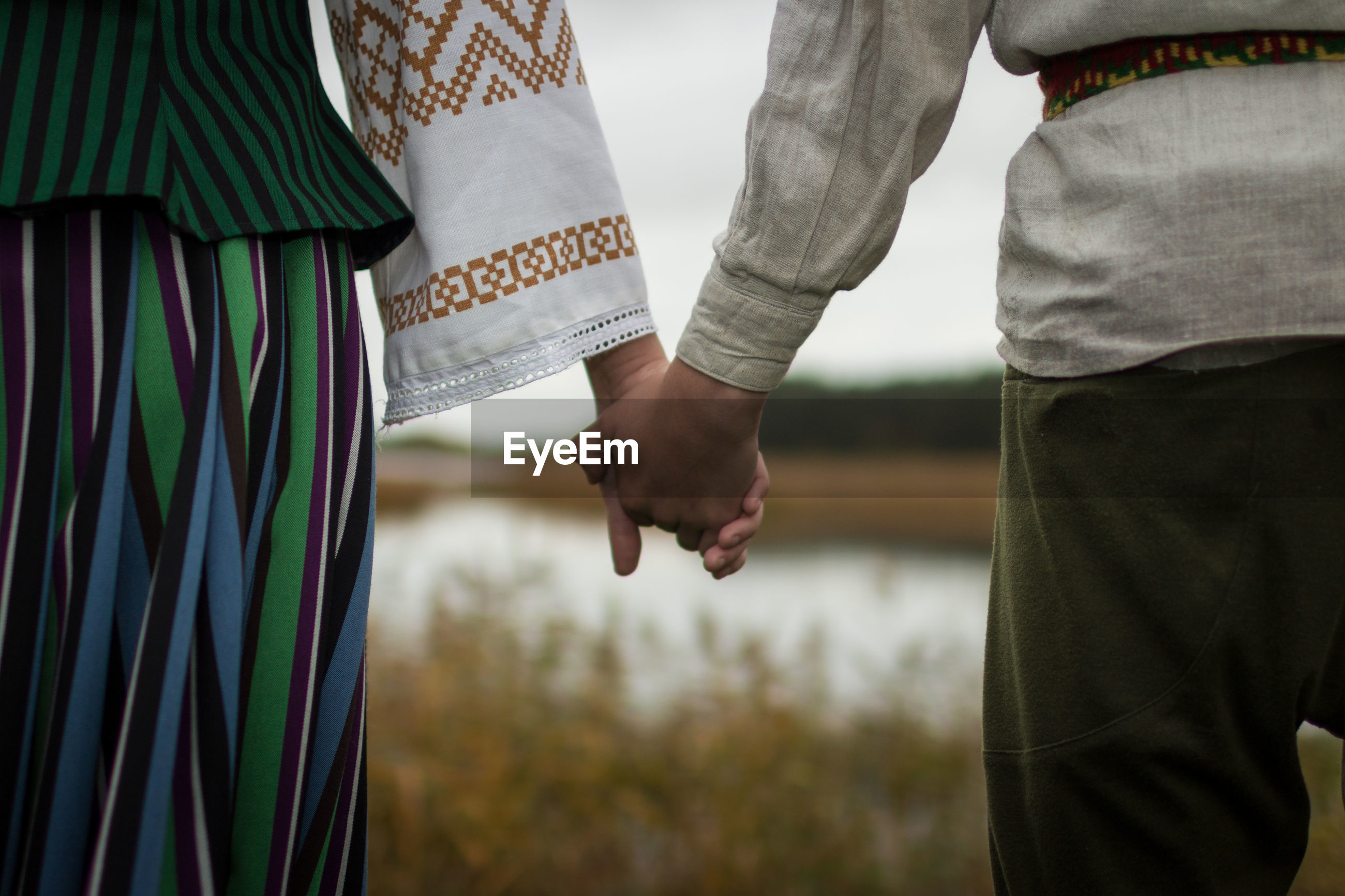 Midsection of couple holding hands while standing at lakeshore