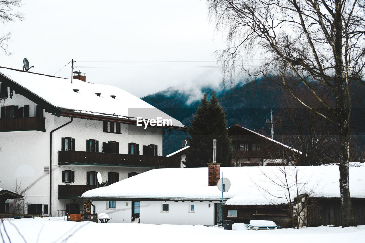cold temperature, building exterior, winter, architecture, snow, built structure, building, tree, day, nature, house, sky, residential district, white color, plant, no people, mountain, covering, frozen, outdoors, snowcapped mountain, snowing