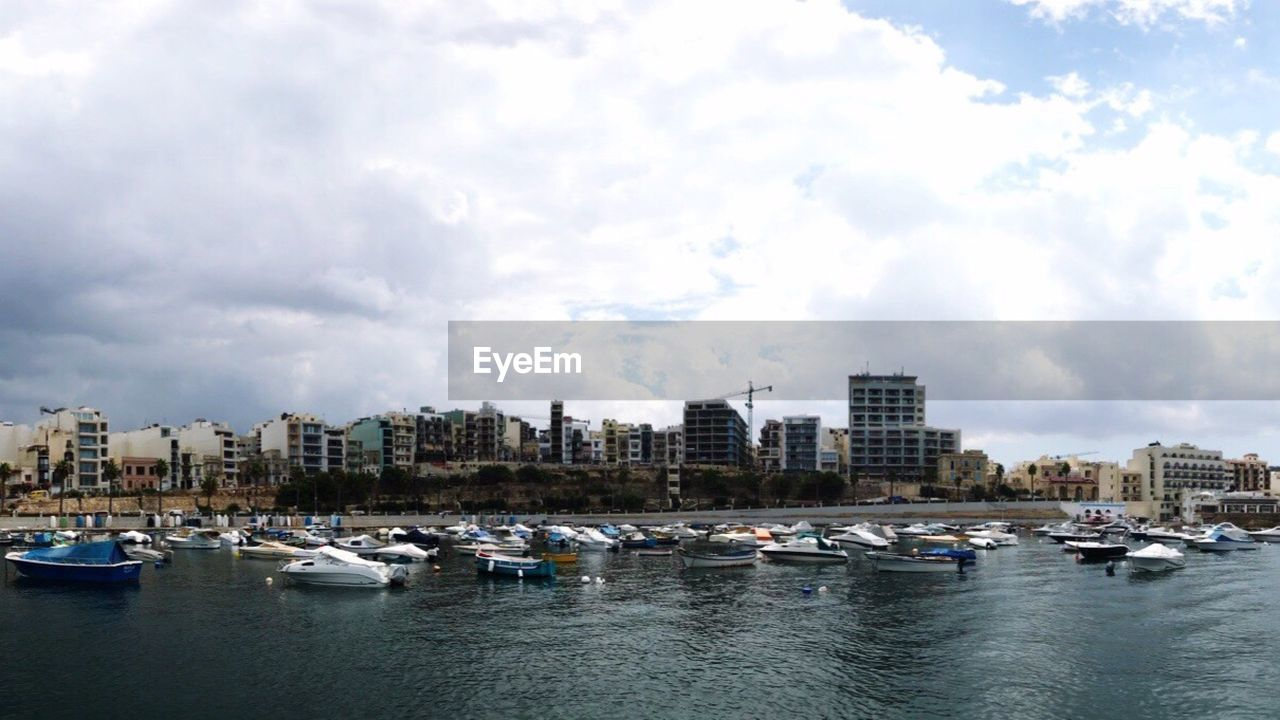 architecture, nautical vessel, building exterior, sky, mode of transport, built structure, transportation, city, water, no people, waterfront, cloud - sky, moored, day, outdoors, skyscraper, cityscape, nature