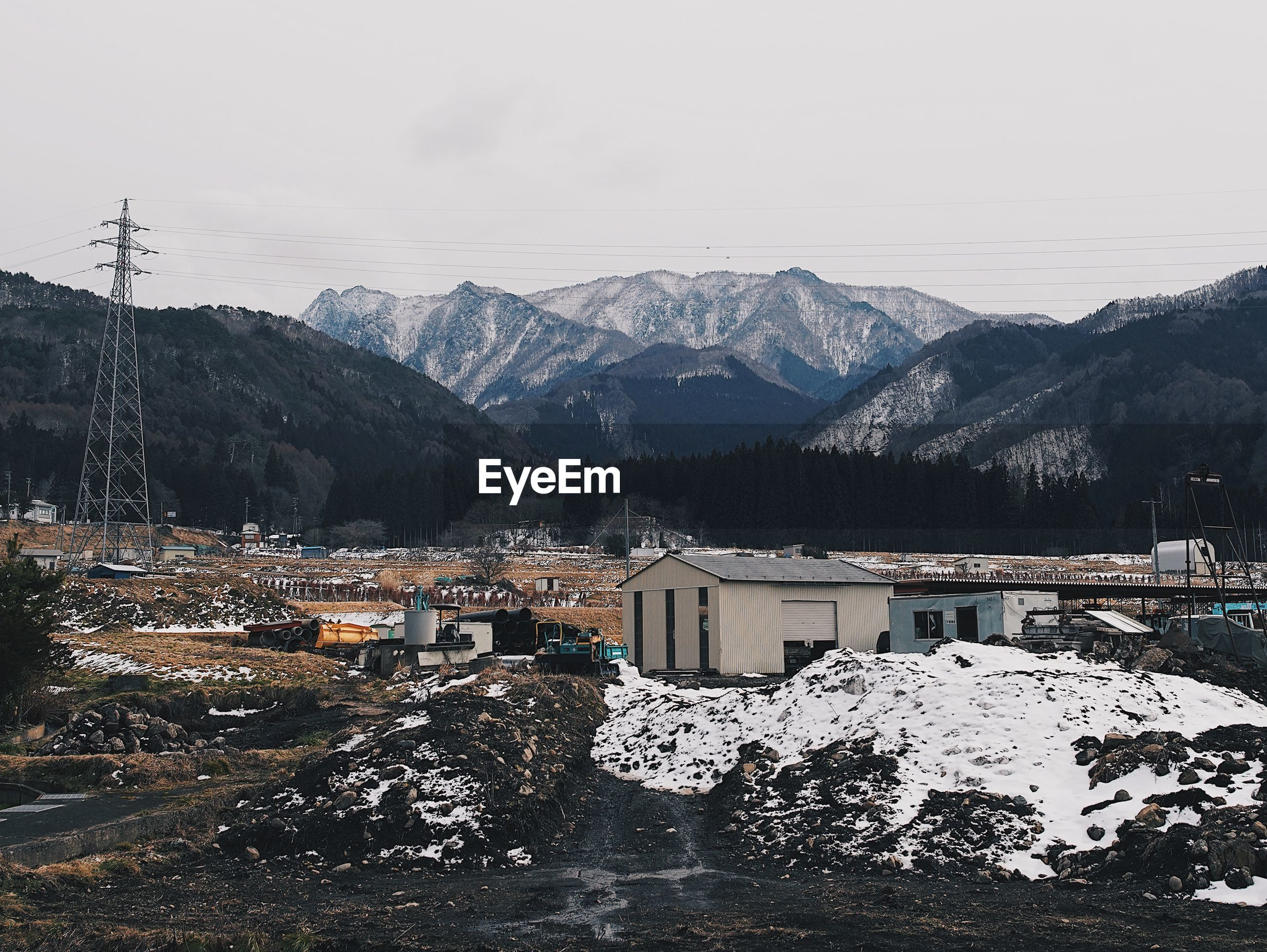 Scenic view of buildings and mountains against sky during winter