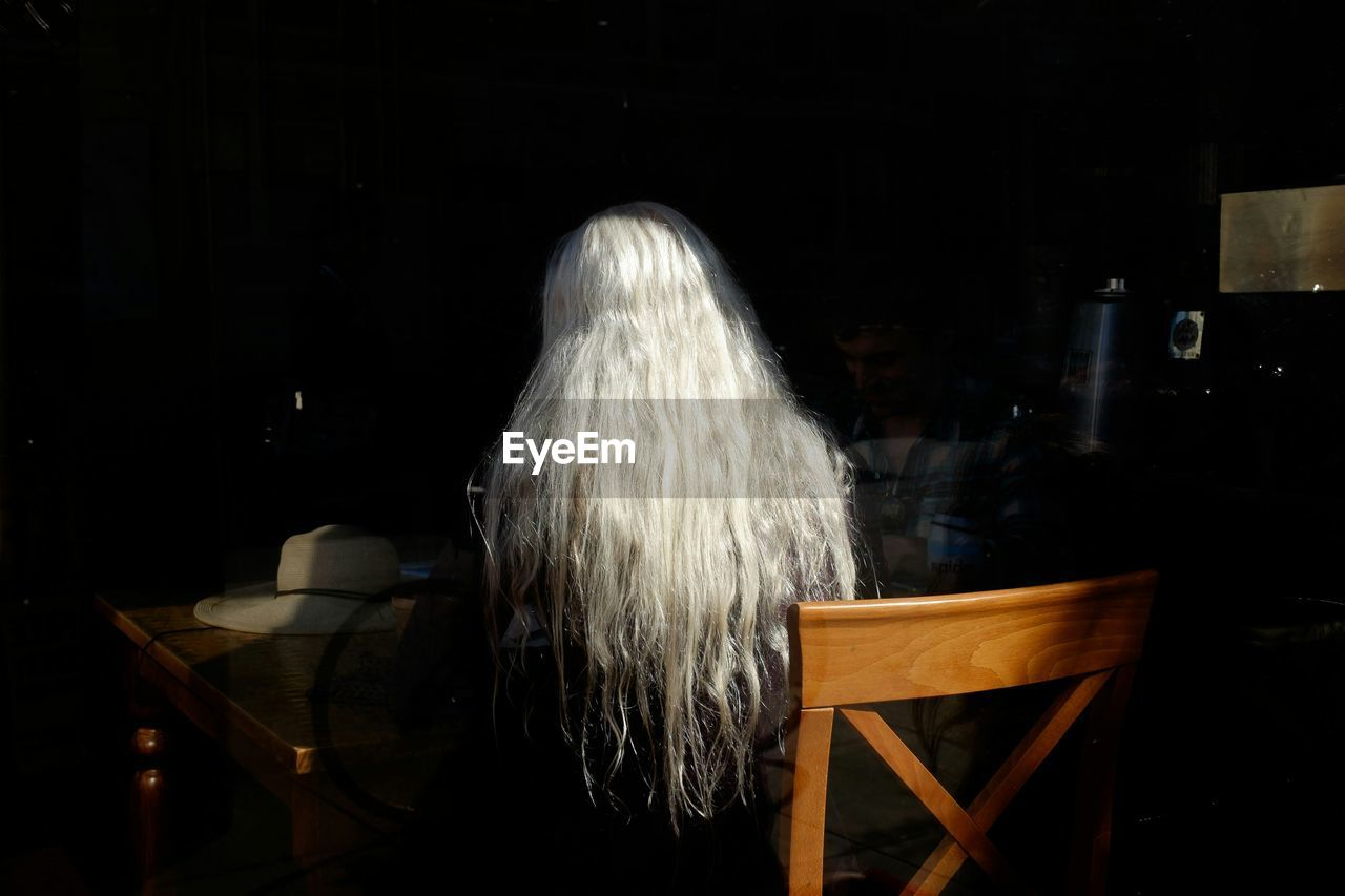 Rear view of person with white long hair sitting in restaurant