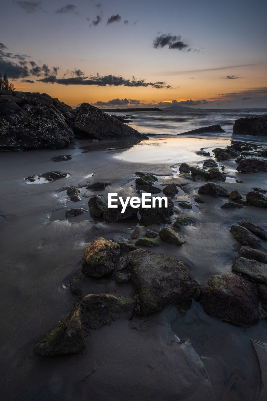 sky, water, sunset, beauty in nature, scenics - nature, rock, sea, solid, rock - object, cloud - sky, beach, tranquility, tranquil scene, land, no people, long exposure, nature, motion, idyllic, horizon over water, rocky coastline