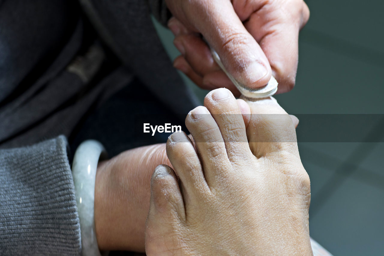 Midsection Of Woman Cleaning Customer Toe Nails