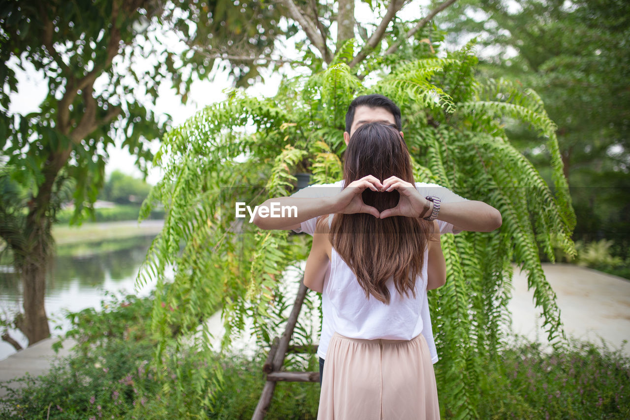 Rear view of woman with man hands making heart shape while standing against plants