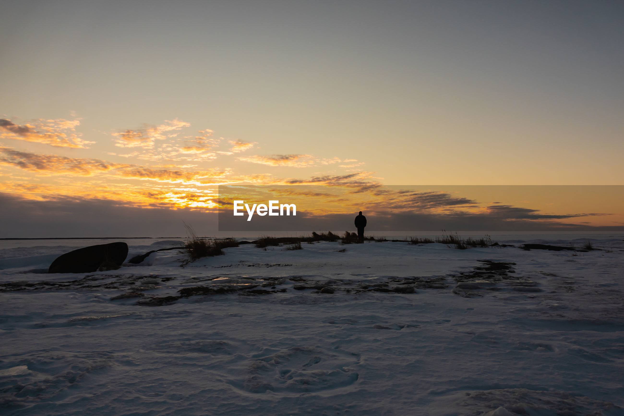Silhouette man standing at snow covered beach against sky during sunset