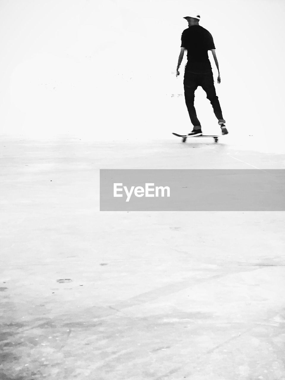 Rear View Of Man Skating On Skateboard Park