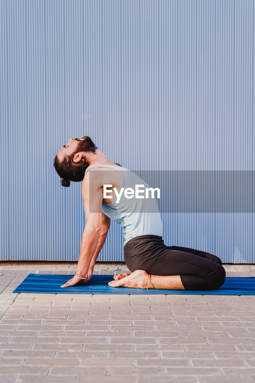 Side view of man doing yoga