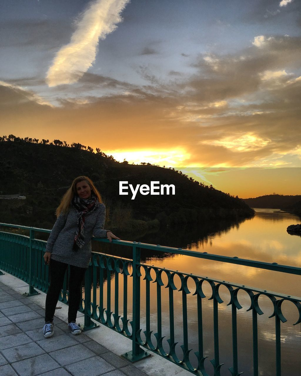 sunset, railing, sky, young women, young adult, cloud - sky, leisure activity, real people, lifestyles, nature, standing, beauty in nature, women, one person, full length, casual clothing, adult, scenics - nature, outdoors, beautiful woman, warm clothing