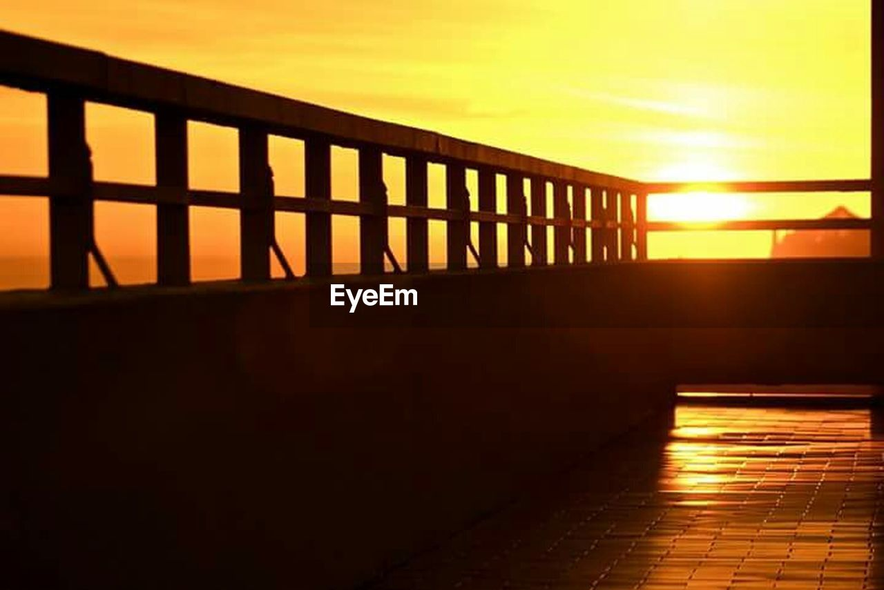 sunset, sun, orange color, railing, sunlight, silhouette, sky, scenics, sea, outdoors, nature, no people, tranquility, built structure, water, beauty in nature, architecture, day