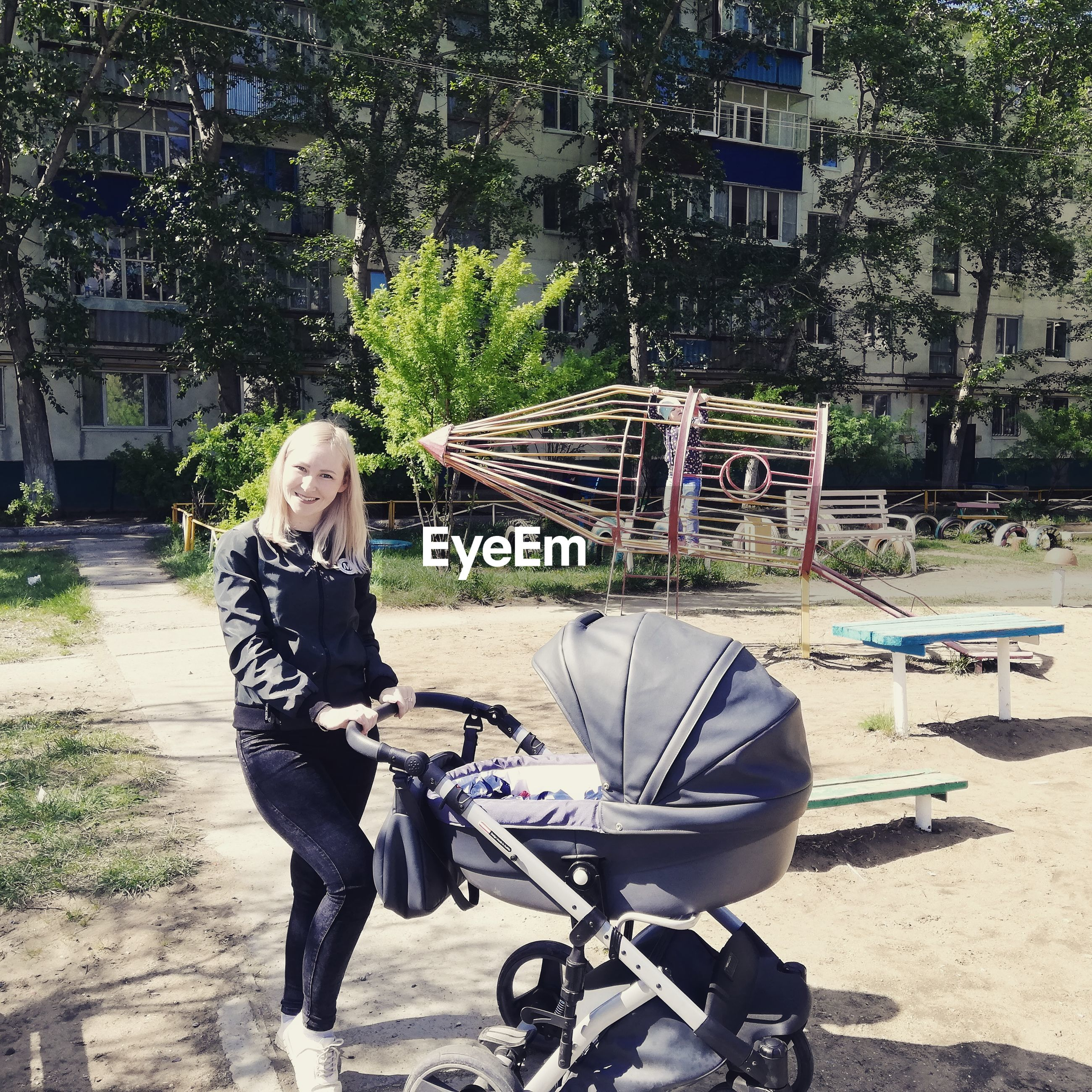 Full length of woman holding baby stroller while standing in city