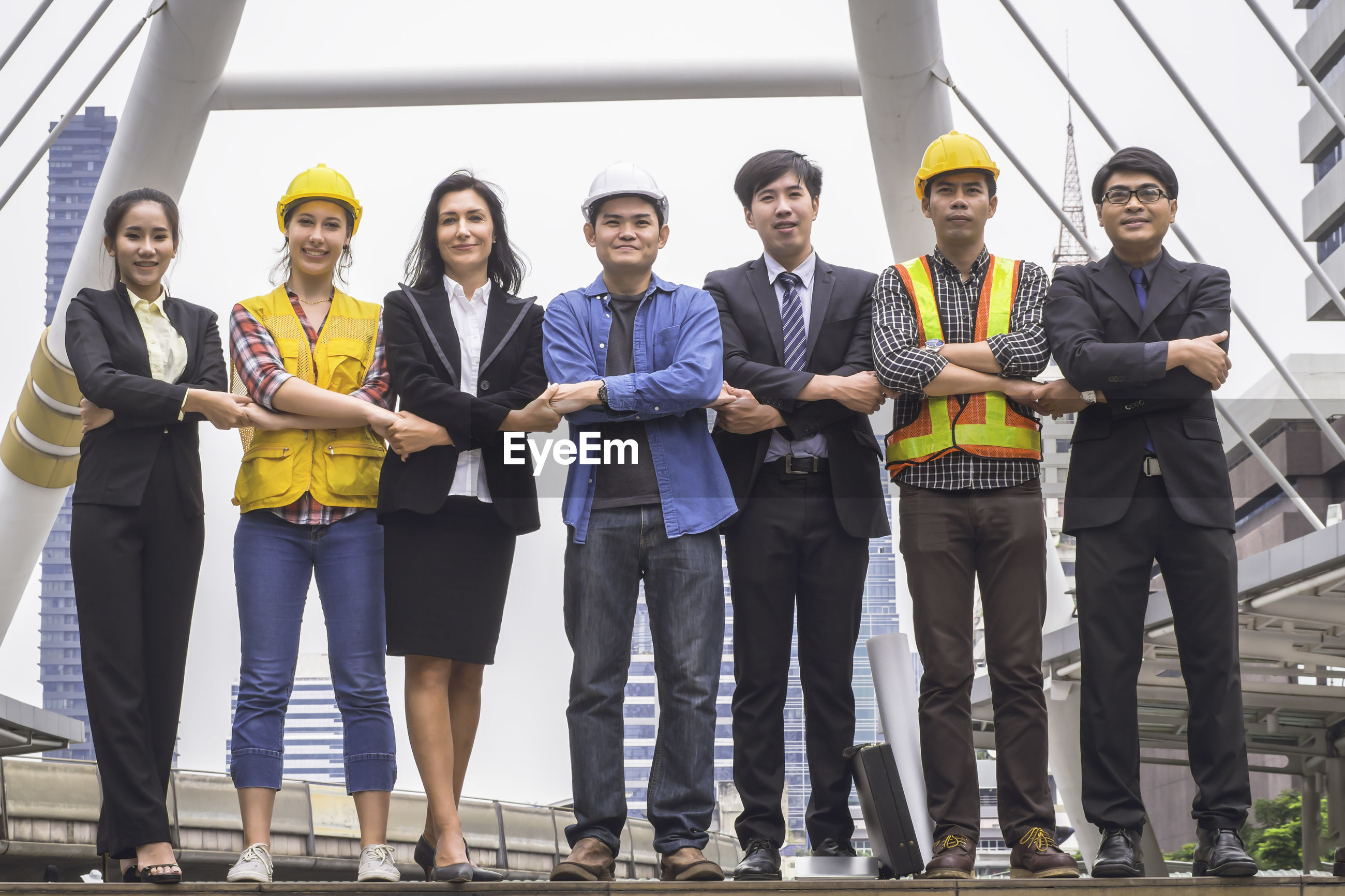 Portrait of smiling engineers and business people standing outdoors