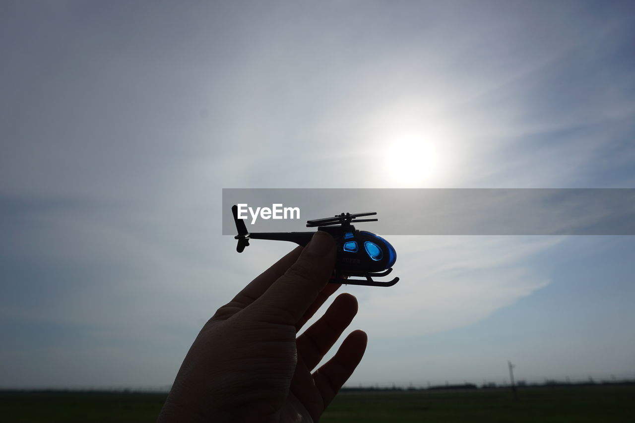 sky, human hand, hand, one person, real people, holding, human body part, unrecognizable person, nature, sun, cloud - sky, sunlight, personal perspective, sunset, finger, leisure activity, human finger, lifestyles, outdoors, lens flare